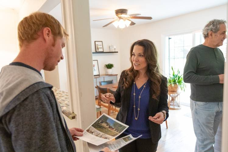 Redfin Agent Yvette Evans, center, talks with a prospective home buyer during an open house in Austin, Texas, on Sunday.
